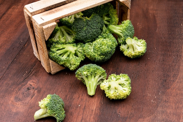 Sliced broccoli in wooden box on wooden floor