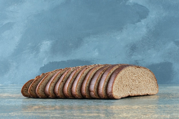 Sliced brown bread on marble background