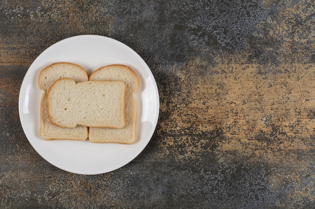 Sliced brown bread on white plate.