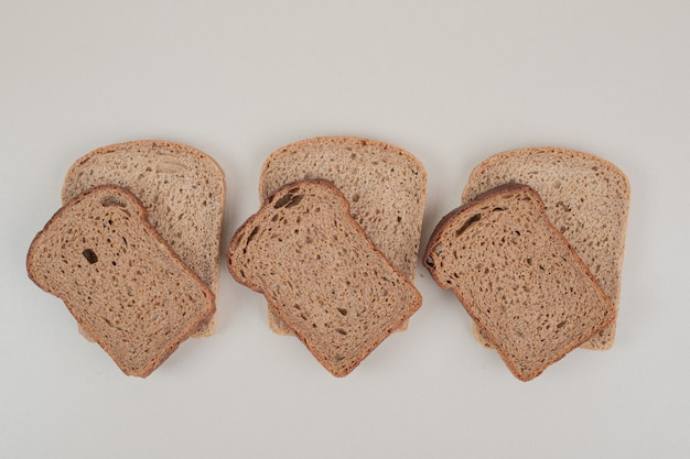 Sliced brown bread on white surface