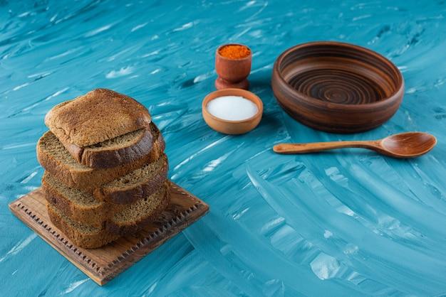 青い背景に塩と空の木のスプーンでスライスした茶色のパン。