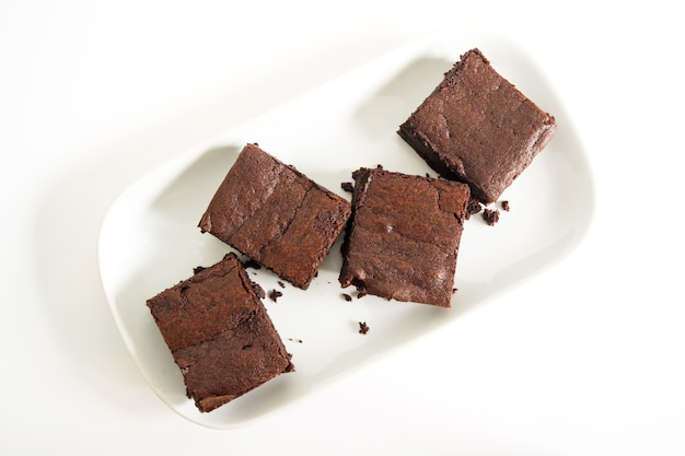 Sliced brownies on white plate. on white plate over white background. top view.