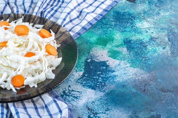 차 타월에 접시에 얇게 썬 양배추와 당근