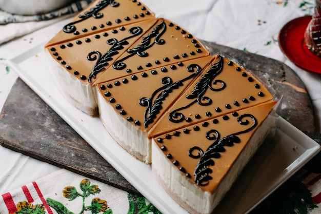 Pezzi di torte a fette marrone progettato delizioso panna squisita all'interno piatto bianco sul tavolo colorato tè caldo