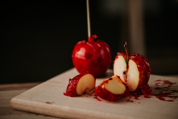 Sliced candy apples on wooden board.