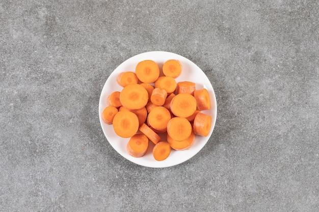 Нарезанная морковь на тарелке, на мраморе.