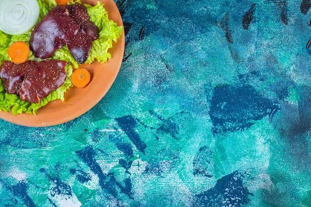 Carota affettata, foglie di lattuga cipolla e fegato di pollo su una ciotola di argilla