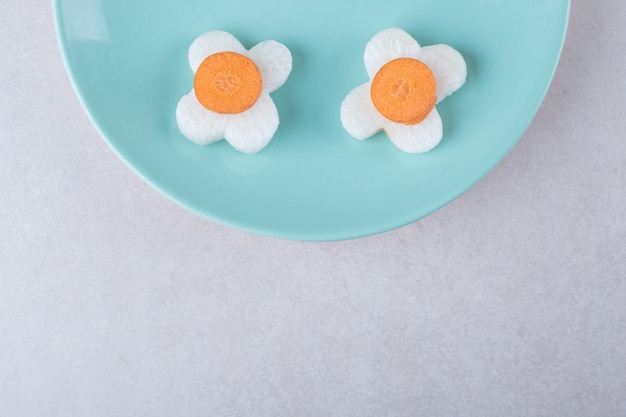 Нарезанные морковь, редис и зеленый перец чили на тарелке на мраморном столе.