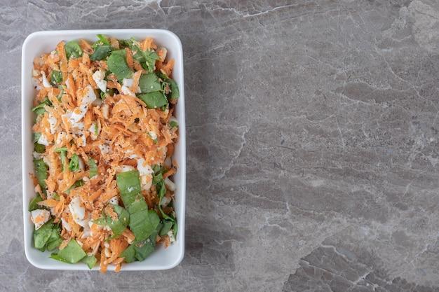 Insalata di carote a fette sul piatto bianco.