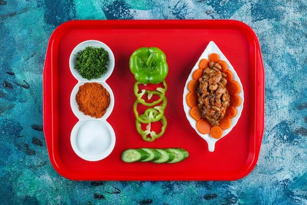 블루 테이블에 쟁반에 접시에 당근, 콩, 야채를 썰어.