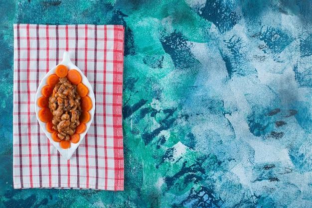 青の背景に、ティータオルのプレートにニンジンと豆をスライスしました。