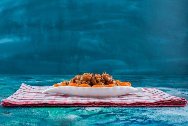 青いテーブルの上で、ティータオルの皿にニンジンと豆をスライスしました。
