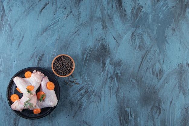 Нарезанная морковь и куриное крылышко на тарелке рядом с миской для специй, на синем фоне.