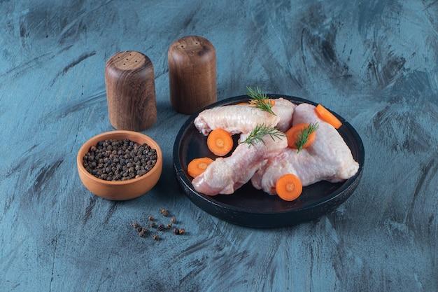 Нарезанная морковь и куриное крылышко на тарелке рядом с миской для специй, на синей поверхности.