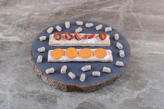 Нарезанная морковь и помидоры на хрустящем хлебе, окруженные крошкой на доске, на мраморной поверхности