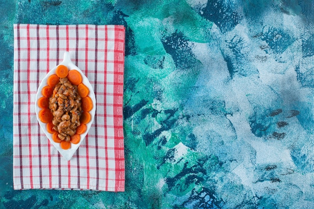 Sliced carrots and beans on a plate on the tea towel , on the blue background.