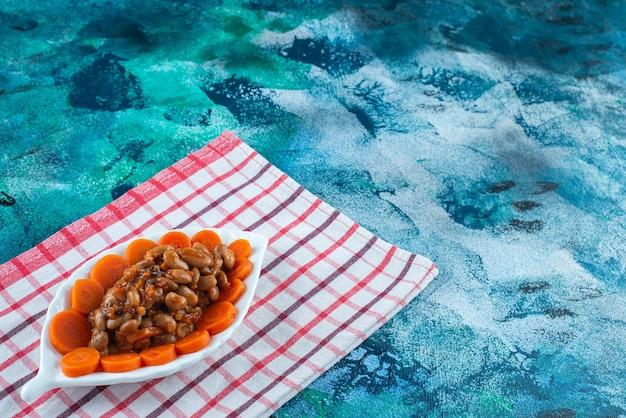 Carote e fagioli affettati su un piatto sul canovaccio, sul tavolo blu.