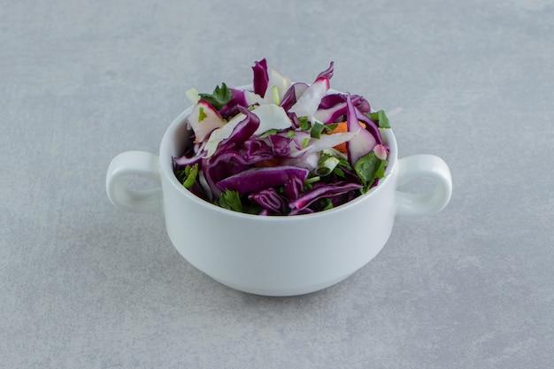 대리석 배경에 당근, 양배추, 채소를 컵에 썰어 놓았습니다.