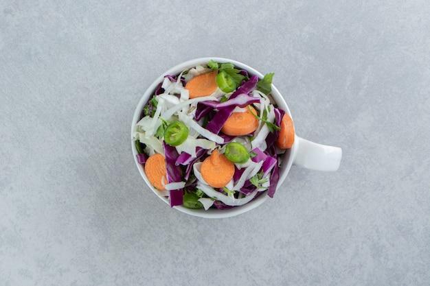Нарезанные морковь, капуста, зелень, в чашке, на мраморе.