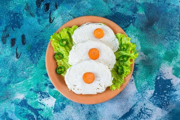 Carote affettate, cavoli e foglie di lattuga su un piatto