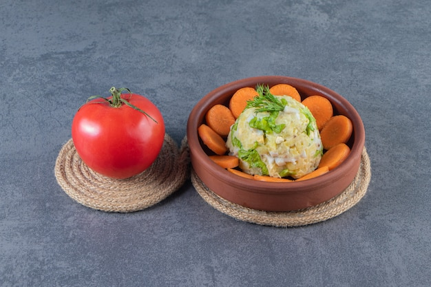 Sliced carrots and capital salad in a bowl next to tomatoes on trivet on the blue surface