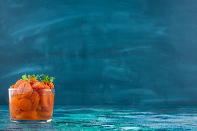 Нарезанная морковь в стакане, на синем столе.