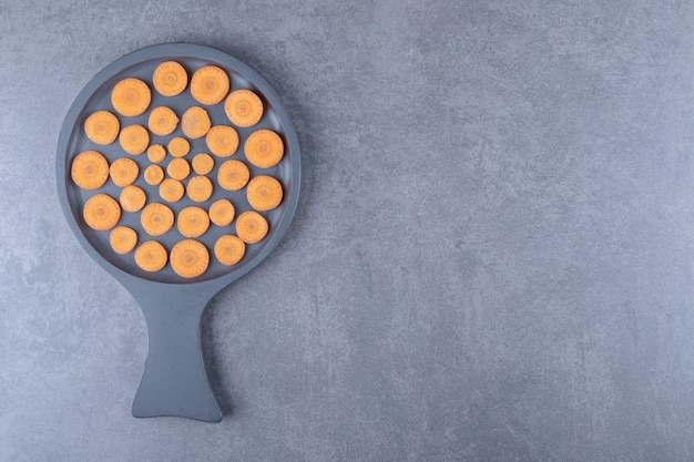 Sliced carrots in a pan, on the marble background.