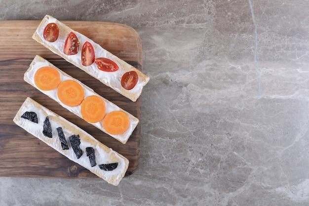 大理石の表面に、カリカリのパンにニンジン、プルーン、トマトをスライスしました