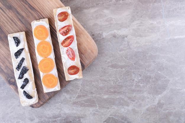 Carote, prugne e pomodori a fette su pane croccante, sulla superficie di marmo