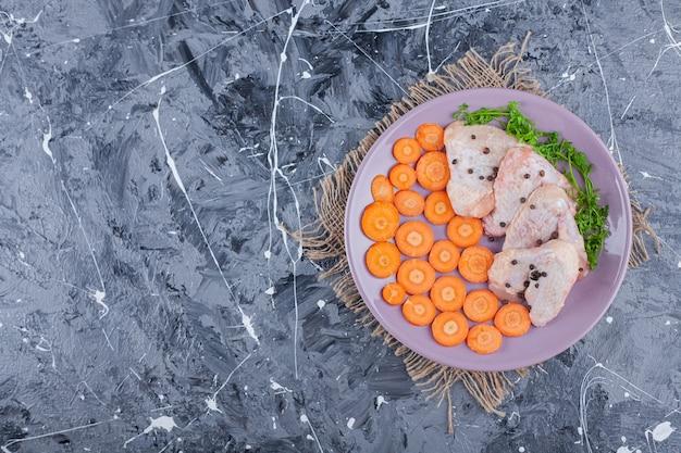 Carote, ali e verdure a fette su un piatto su una tela sulla superficie blu