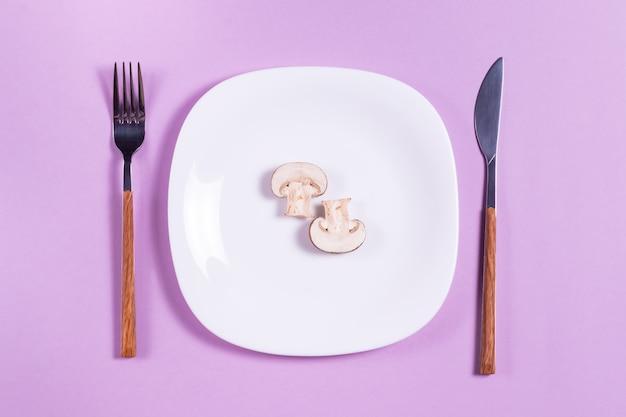 紫のテーブルにカトラリーと白い皿にシャンピニオンをスライス