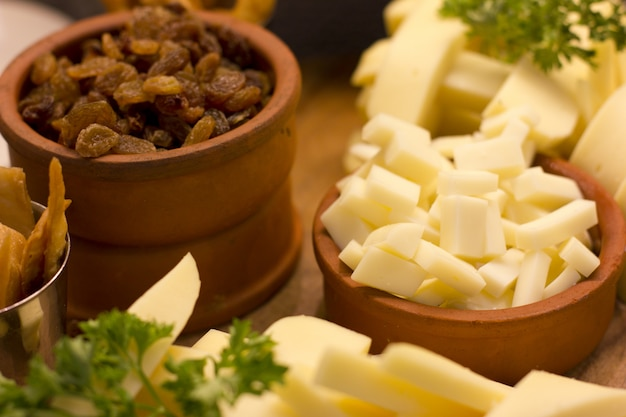 Sliced cheddar cheese and raisins in clay bowls. selective focus