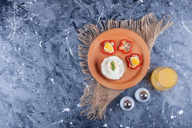 Fette di pane al formaggio e pepe su un piatto accanto a un bicchiere di succo, su sfondo blu.