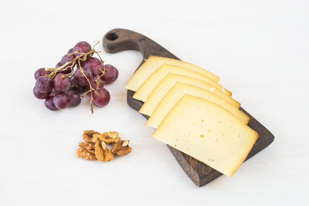 Sliced cheese with grapes and nuts on rustic table.