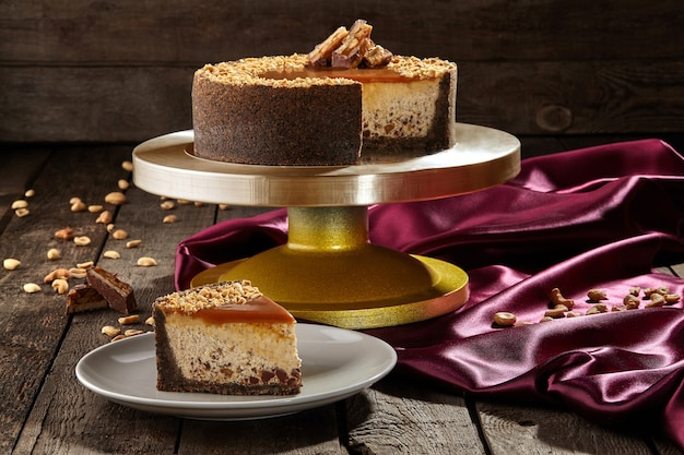 Sliced cheesecake with chocolate crumbs peanuts and caramel