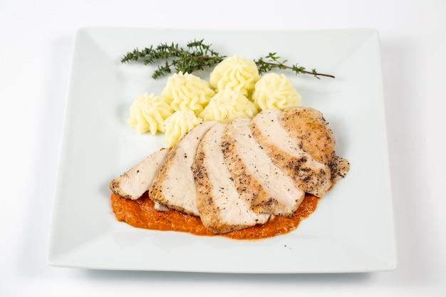 으깬 감자와 함께 소스에 닭 가슴살 슬라이스