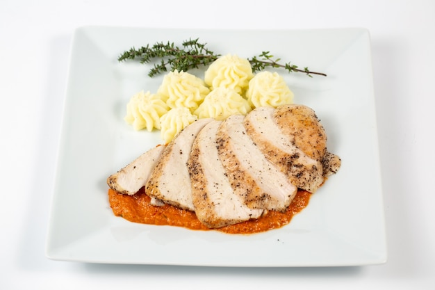 Sliced chicken breast in a sauce with mashed potatoes