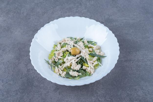 Нарезанный куриный салат на белой тарелке.