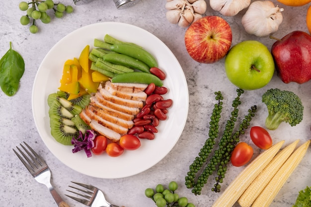 Sliced chicken steak with peas, tomatoes, kiwi and pumpkin.