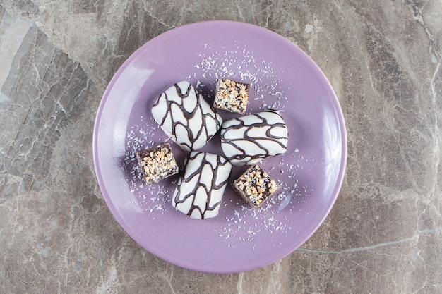 대리석에 나무 접시에 견과류와 함께 슬라이스 초콜릿 바.