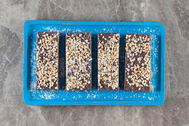 Tavoletta di cioccolato a fette con noci sul piatto di legno su marmo.