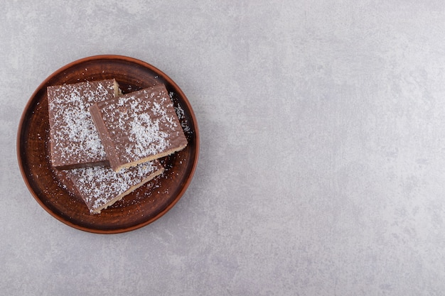 돌 테이블에 배치하는 갈색 접시에 초콜릿 케이크를 슬라이스.