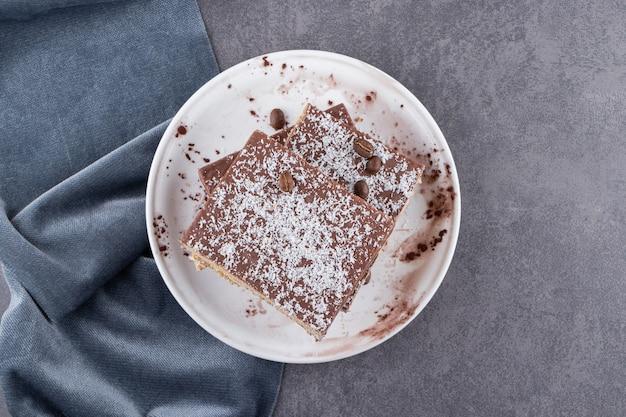 돌 테이블에 배치하는 흰색 접시에 초콜릿 케이크를 슬라이스.