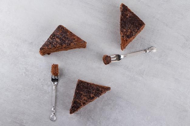 돌 테이블에 놓인 포크로 초콜릿 케이크를 슬라이스.