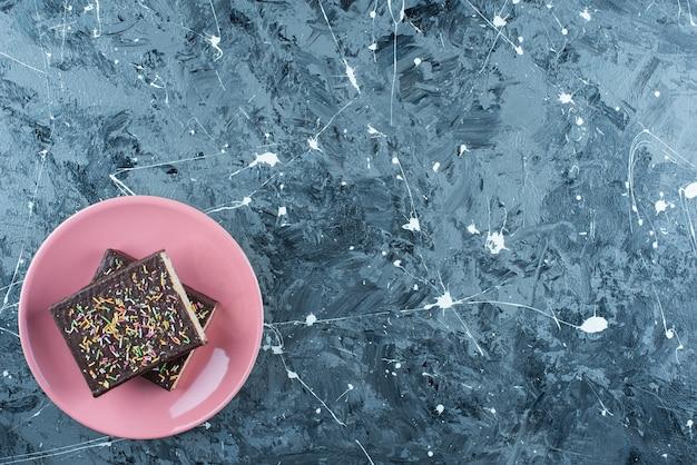 파란색 테이블에 접시에 초콜릿 코팅 와플을 슬라이스.