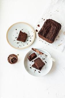 Ломтик шоколадного торта подается на двух тарелках, нож покрыт шоколадом