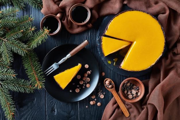 スライスしたチョコレートマンゴーチーズケーキ。黒いプレートにデザートフォークとチョコレートチップを添えたチーズケーキ。モミの木と木製のテーブルの上のコーヒーとカップ、上からの眺め、フラットレイ