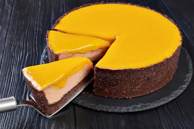 スライスしたチョコレートマンゴーチーズケーキ。黒い木製のテーブルの上の黒い石のプレート上のケーキのシャベルの部分、上からの眺め、クローズアップ