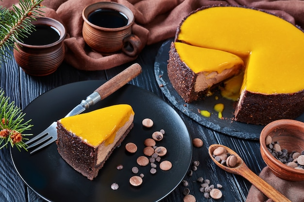 Sliced chocolate mango cheesecake. a piece of a cake served on a black plate with dessert fork and chocolate chips. fir tree and cups with coffee on a wooden table, view from above,  close-up