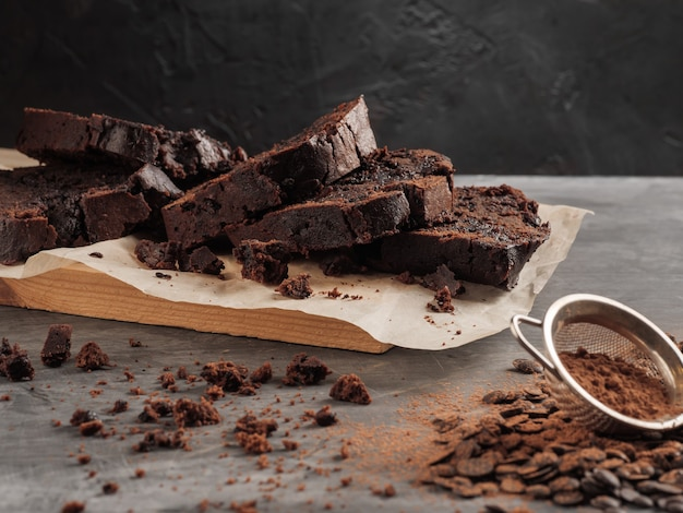 A sliced chocolate pound cake stands on a gray table with chocolate chips and cocoa.
